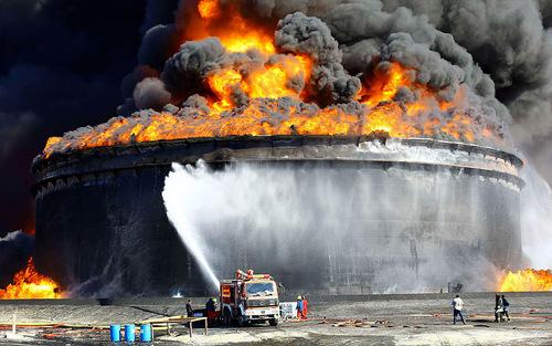 اصابت یک راکت به یک مخزن  بزرگ نفت در لیبی و تلاش آتش نشانان برای خاموش کردن آتش
