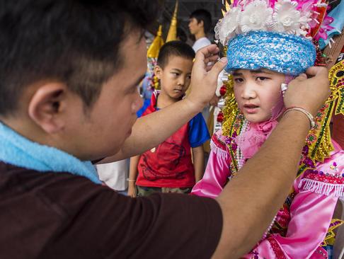 پوشیدن لباس های سنتی در جریان یک جشنواره آیینی در تایلند