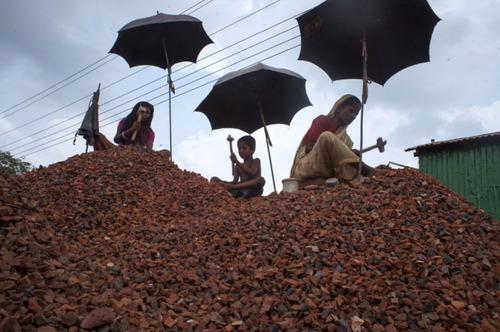 زنان کارگر بنگلادشی در حال شکستن آجر ساختمان های تخریب شده . مزد 10 ساعت کار روزانه برای این زنان روزانه 2 دلار است (شهر داکا)