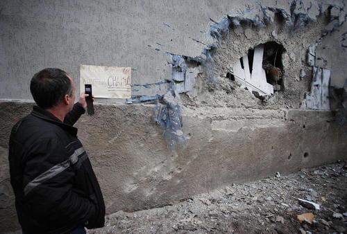 گرفتن عکس از یک دیوار تخریب شده در اثر حملات خمپاره ای (شهر دونتسک در شرق اوکراین)