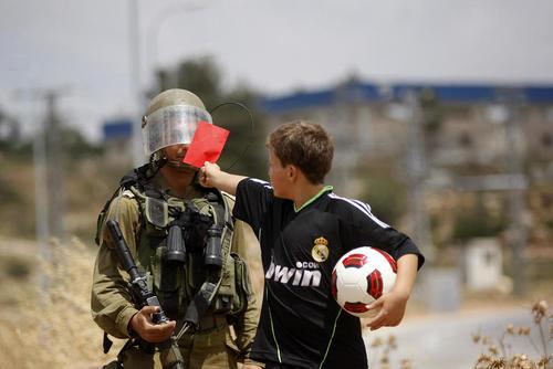 کارت قرمز نوجوان فوتبالیست فلسطینی به سرباز اسراییلی در اعتراضات علیه فدراسیون فوتبال اسراییل در رام الله