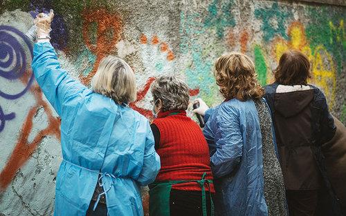 زنان هنرمند در حال خلق یک نقاشی دیواری بزرگ در شهر لیسبون پرتغال