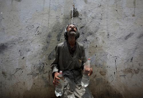یک مرد پاکستانی در حال خنک کردن خود در گرمای شدید کراچی پاکستان. گرما در پاکستان باعث مرگ بیش از 400 نفر شده است.