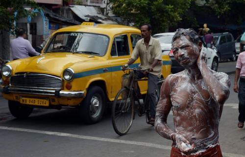 مرد هندی با استفاده از آب شهرداری در حال حمام کردن در یکی از خیابان های کولکاتا