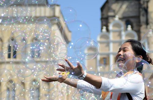 یک توریست آسیایی در حال بازی با حباب در میدان قدیمی شهر پراگ – جمهوری چک