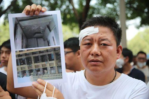 یک شهروند چینی در شهر تیانجین در حال نشان دادن تصویر خانه اش قبل و بعد از انفجار مهیب اخیر تیانجین
