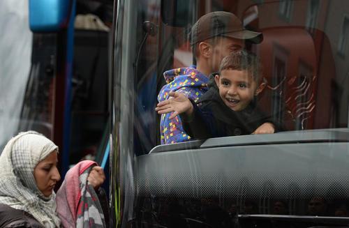 انتقال دهها مهاجر سوری تازه رسیده از ایستگاه قطار شهر مونیخ آلمان با اتوبوس به محل های اسکان موقت