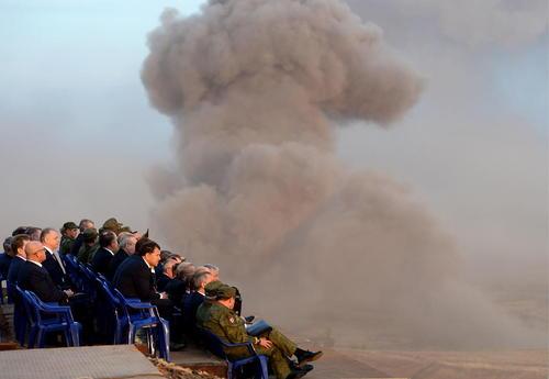 ولادیمیر پوتین رییس جمهور روسیه و جمعی از ژنرال های ارشد ارتش روسیه در حال تماشای یک رزمایش نطامی
