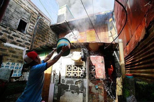 خاموش کردن آتش سوزی خانه در یک منطقه حومه ای در شهر پاراناگ فیلیپین