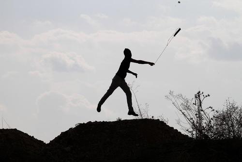 جوان فلسطینی در حال پرتاب سنگ به سمت سربازان اسراییل – کرانه غربی