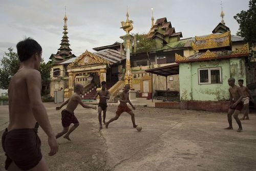 راهبان بودایی در حال بازی فوتبال در حیاط یک معبد در شهر یانگون میانمار