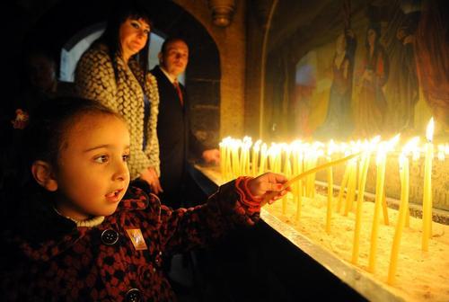 روشن کردن شمع برای صلح در کلیسایی در دمشق در مراسم جشن میلاد مسیح