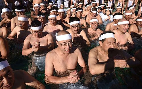 نیایش هواداران آیین شینتو درون استخر آب یخ در جشن سال نو – توکیو