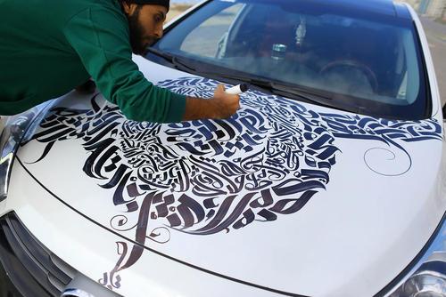 بلال خالد هنرمند گرافیست غزه ای در حال رنگ آمیزی یک خودرو