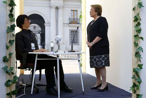 میشل باشله رییس جمهوری شیلی در حال صحبت با یک روبات ژاپنی در مراسم افتتاح نمایشگاه آینده در شهر سانتیاگو