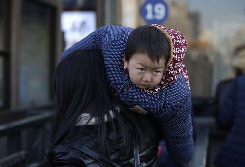 مادر و فرزند در حال سوار شدن به قطار در ایستگاه قطار پکن