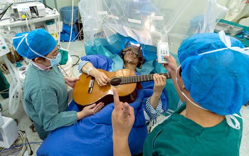 مرد 57 ساله چینی در شهر شنزن زیر عمل جراحی مغز در حال نواختن گیتار است. این هفتمین عمل جراحی به روش