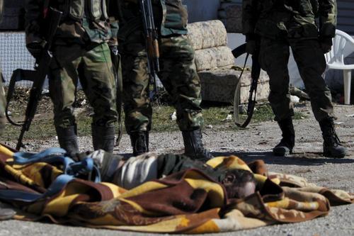 نیروهای ارتش سوریه بالای سر یک شورشی مسلح کشته شده پس از آزادی شهر ربیه در استان لاذقیه از دست گروه های مخالف حکومت سوریه