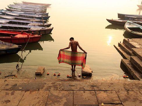 یک مرد هندو در حال انجام آیین آب تنی در حاشیه رود گنگ در واراناسی هند