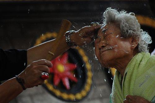 پاشیدن آب روی صورت زائران معبدی در سورابایای اندونزی