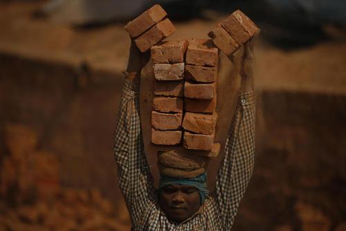 یک کارگر مهاجر ساختمانی در حال جابجایی آجر در شهر زلزله زده باختاپور نپال