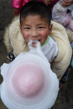 کودک روستایی چینی در حال خوردن آب نبات پنبه ای (پشمکی) در جشن سال نو چینی