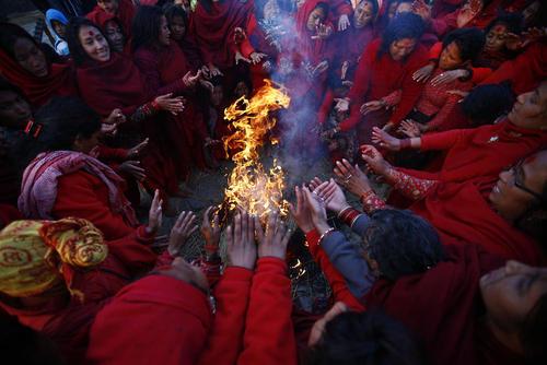 گرم شدن زائران بودایی در نپال پس از آب تنی آیینی