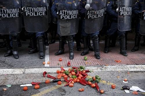 پرتاب محصولات کشاورزی از سوی کشاورزان اعتصاب کننده یونانی به صف پلیس ضد شورش در مقابل ساختمان وزارت کشاورزی در شهر آتن