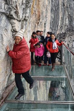 عبور توریست ها از پل شیشه ای 1 کیلومتری در ارتفاع 100 متری در یک پارک ملی در استان گویژو