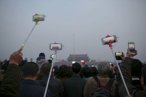 گرفتن عکس از مراسم برافراشته شدن پرچم چین در میدان تیان آن من پکن همزمان با برگزاری نشست کنگره ملی خلق این کشور