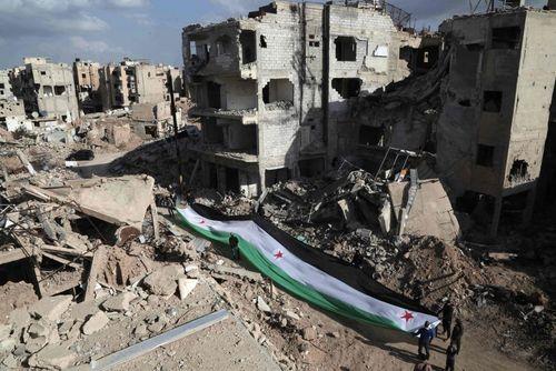 مخالفان مسلح حکومت سوریه پرچم سابق این کشور را در ویرانه های شهر جُبار در حومه شرقی دمشق پهن کرده اند