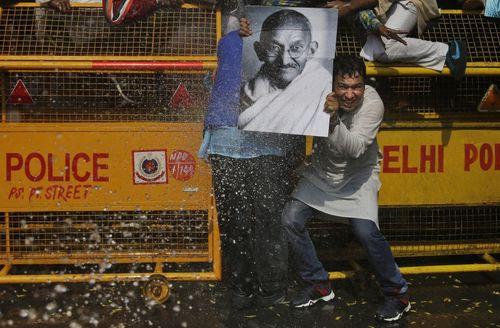 یک تظاهرات کننده حزب کنگره هند تابلوی تصویر مهاتما گاندی رهبر استقلال هند را برای امان ماندن از ماشین آب پاش پلیس هند در مقابل خود گرفته است