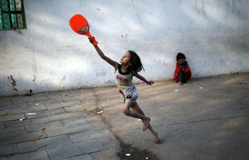 دختری در حال بازی بدمینتون در یکی از خیابان های دهلی