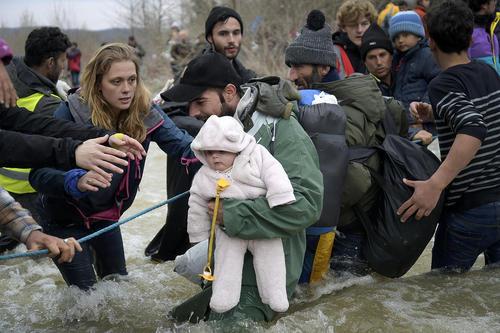 پناهجویان خاورمیانه ای در حال عبور از عرض یک رودخانه پس از گذشتن از مرز یونان و مقدونیه