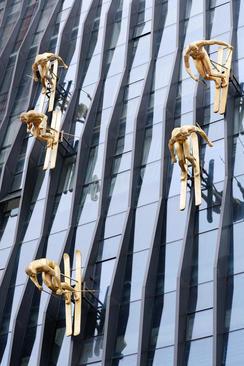 مجسمه های اسکی بازهای برنزی روی نمای ساختمانی در شهر چونگینگ چین