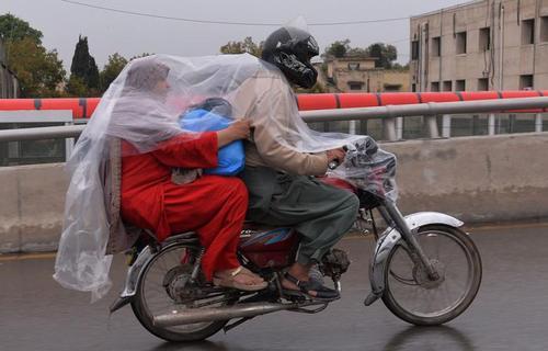 زوج موتورسوار در خیابانی در شهر راولپندی پاکستان