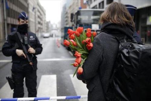 زنی گل در دست در حال حرکت به سمت محل یادبود قربانیان انفجارهای سه شنبه بروکسل