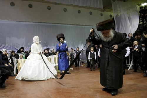 یک عروس یهودی ارتدوکس افراطی در مراسم «میتزوا تانتز» یا مراسم رقص در اسرائیل. مراسمی که در آن نزدیکان عروس بعد از مراسم عروسی در برابر او می رقصند. این مراسم در نتانیا در اسرائیل برگزار شد. هزاران نفر از جمله رهبران مذهبی در این مراسم شرکت داشتند. عکس از باز راتنر/ رویترز