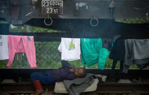 کودکی دراز کشیده بر روی ریل راه آهن در اردوگاه موقت مهاجران و پناهجویان در مرز یونان با مقدونیه. عکس از اندریه ایزاکوفیچ - خبرگزاری فرانسه