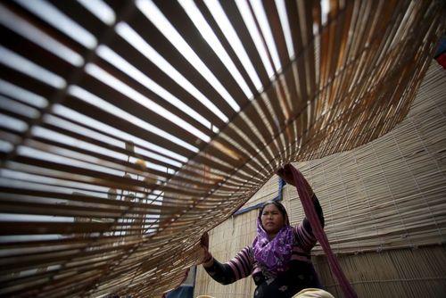 یک زن هندی در حال درست کردن پرده های حصیری از چوب بامبو