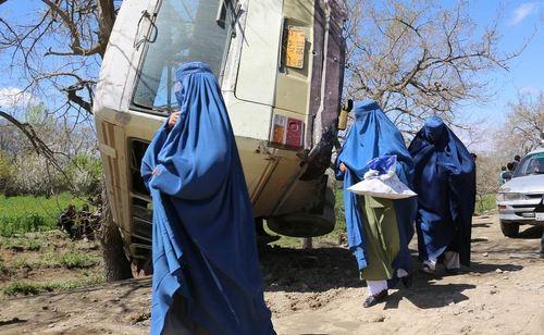 عبور زنان افغان از کنار مینی بوس واژگون شده طی انفجار بمب در کابل افغانستان
