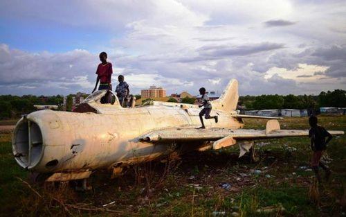 کودکان شهر جوبا در جنوب سودان در حال بازی با یک هواپیمای جنگی ساقط شده