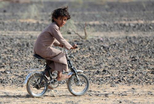 دوچرخه سواری کودک پاربرهنه یمنی در شهر مارب