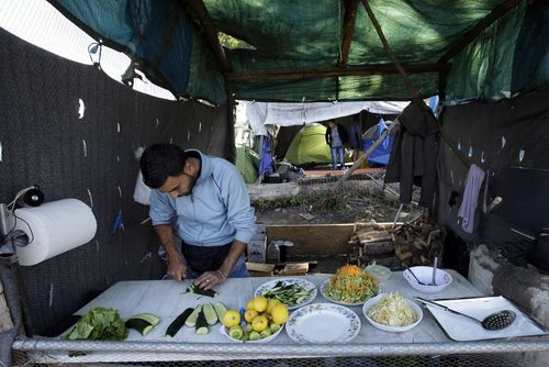 مرد پناهجوی سوری در حال آشپزی در آشپزخانه صحرایی در مرز یونان و مقدونیه