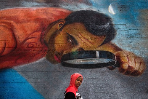 زن لبنانی در حال عبور از کنار یک نقاشی دیواری در بیروت