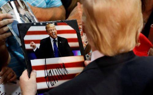 دونالد ترامپ نامزد احتمالی جمهوریخواهان برای انتخابات ریاست جمهوری آمریکا در حال امضای عکسش در جمع هوادارانش در ایالت اورگان