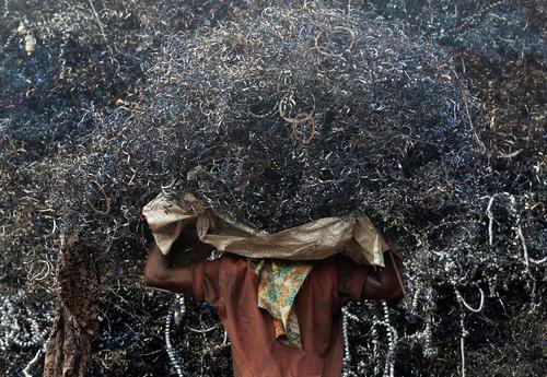 یک کارگر در حال حمل آهن قراضه – بمبئی