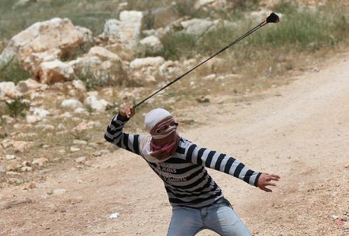جوان فلسطینی در حال پرتاب سنگ به سمت سربازان اسراییل – نابلس