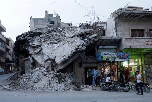 یک بوتیک لباس فروشی در کنار ساختمان ویران شده از جنگ در شهر مارت النعمان در استان ادلب سوریه که در کنترل شورشان مخالف حکومت است