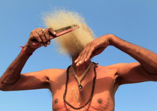 شانه زدن ریش پس از آب تنی مرد هندو در رود – هند